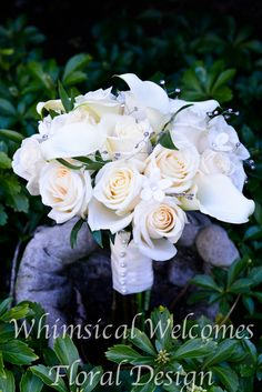 An all white bouquet of roses, calla lilies, stephanotis with rhinestones, ruscus, and sprays of rhinestones.
