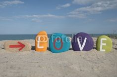 Love direction, message on colourful stones with beach background