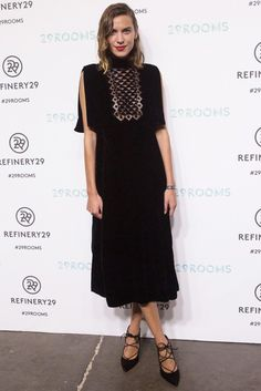 Alexa Chung wears a black high-neck midi dress by Valentino with lace-up black pumps