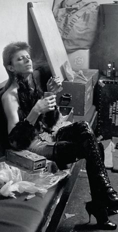 David Bowie smoking in thigh-high leather boots.
