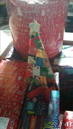 Scraps of wrapping paper in corrugated card triangle to make Christmas tree decoration.