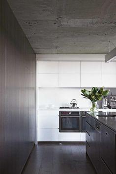 Kitchen: concrete ceiling, white handleless cabinets, white stone splashback, dark wooden floorboards, dark wood veneer concealed cabinetry