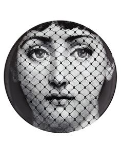 Printed black and white porcelain wall plate from Fornasetti featuring a womans face.