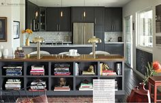 Dark gray-blue kitchen with open shelves on living room side.  Styled with lamps and contrasted with wood and white counters