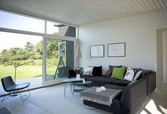 LUFTIG STUE: I stuen kan familien slappe av i en rommelig sofa fra Bolia. Det grå ullstoffet lives opp av fargerike puter fra Hay og Anne Nowak - en kjent, dansk tekstilkunstner. Bordet er kjøpt på Designer Zoo. Lampen over bordet er fra Secto Design.