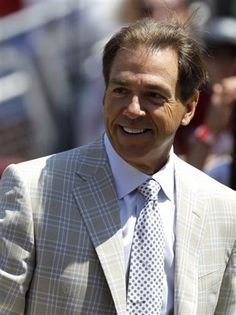 Nick Saban smiles as he walks onto the field before Alabama's spring game.