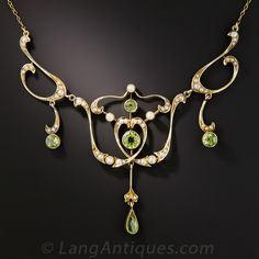Sinuous lines, lustrous pearls and bright lime green peridots join forces to create this alluringly feminine, original Art Nouveau necklace - circa 1900. The centerpiece measures over 2 1/8 inches from the top pearl to the teardrop dangle. Lightly hand-fabricated in 15K gold, hence very likely of English origin. 16 inches long and ultra-lovely.
