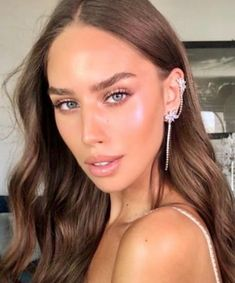 Model is in Nude Envie natural glam and wearing a statement earring. Achieve this natural lip with lip liner, Perfect, and lip gloss, Illuminate