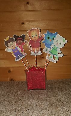 Daniel Tigers Neighborhood Centerpieces Perfect for centerpieces for guest tables, buffet decoration, cake toppers, diaper cakes, gift baskets and more! I N C L U D E S: 5 Centerpiece Picks (Base NOT included) All 5 characters shown included attached to dowel rod perfect for insertion into any base of your choice such as buckets, cakes, plants, etc.,, O P T I O N S: Single Sided Images (White backing) Double Sided Images ( + $0.75 each) S I Z E: Dimensions: Image Height- Approx 6 inches…