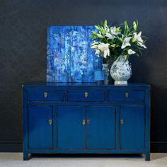 A distressed Chinese sideboard finished in a gorgeous cobalt blue lacquer. This substantial and long cabinet provides useful storage with three large cupboards below three drawers. The cupboards each house a removable shelf and each solid wood door and drawer is furnished with solid brass hardware.