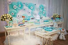 """Na festa com tema """"Frozen"""", produzida pela empresa Balada do Bebê (www.facebook.com/pages/Balada-do-Bebê/253222068040271), a Mirabolar Arte Criativa (www.facebook.com/Mirabolar) confeccionou o painel atrás da mesa do bolo. Feito de rosetas de papel, nas cores branco e azul, elas tiveram aplique de papel rendado em formato de flocos de neve"""
