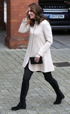 The Duchess looked understated but elegant in a cream coat by Goat worn over a black dress, teamed with knee high boots