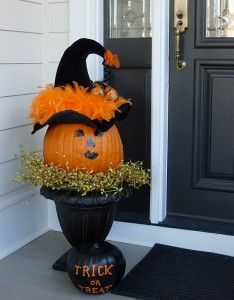 Porch Pumpkin:Start with a black garden urn or planter. Place a wreath of berries or grapevine on the top edge of the wreath.Decorate the face of your pumpkin using a black Sharpie marker or paint.  Be creative and give your pumpkin some real personality.  Position the pumpkin on top of the wreath.  Place a witches' hat on top of your pumpkin.  Secure it with T-pins or small nails if necessary.