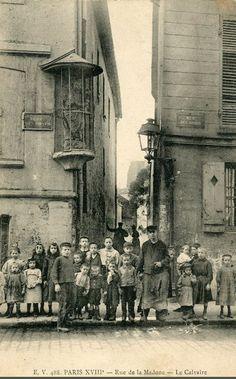 L'étroite rue de la Madone et son calvaire vue depuis la rue des Roses, vers 1905.
