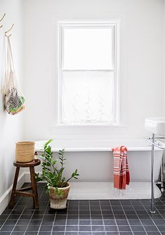 light and lovely bathroom with clawfoot tub, terracotta pot, wooden stool, black tile