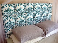 I recently made a padded headboard with ten 12X12 canvases, an old towel for padding, an old curtain and a border of thumbtacks on each square for nail head trim. This is a great tutorial for something similar.