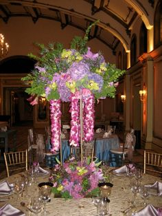 A gorgeous tall floral arrangement of hydrangea, cymbidium orchids, berries, tulips, cattaleya orchid blossoms and hanging leis make up this centerpiece for a wedding at the Langham Hotel Pasadena, CA