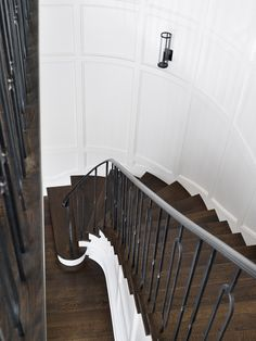 Beautiful curved staircase clad in board and batten boasts an iron hand rail and spindles as well as wooden stair treads.