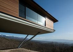 The upper floor of this Japanese mountain home is twice the size of the base, creating a dramatic overhang that looks to be supported by nothing but stilts.