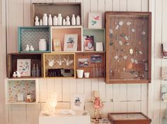 details I like: stacked boxes/crates as shelves, mismatched paint, wallpapered background (very much like paper lining for drawers), origami paper cranes, owl night lamp • The Studio of Mae shop in Stoker Siding, Australia • via Gennine's Art blog