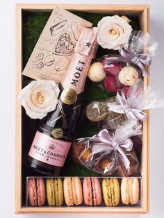 Beautifully assembled gift box featuring champagne, flowers, chocolate and macaroons. A girls dream!