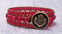 This three row cuff is made of 8mm red glass beads and framed with smaller red glass beads, the leather is a dyed copper gold color and the bracelet is finished with a lovely black and gold coat button.    Fits comfortably up to 7'' to 7 1/4'' wrist  $18.00