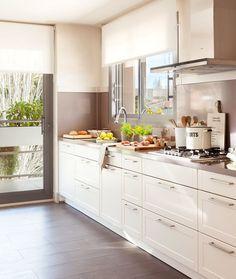 Cocina con muebles dispuestos en un lateral y balcón