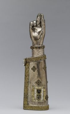 "This silver arm is known as a ""speaking"" reliquary because it takes shape of the body part it once contained. The reliquary reputedly held an arm bone of Saint Pantaleon, a ""Holy Doctor"" martyred in Asia Minor (AD 305) who later became the patron saint of physicians. The remains of an inscription along the seam of the sleeve refer to the saint by name. The small door with the two glass shields was added in the 15th century, as was the crystal at the edge of the sleeve."