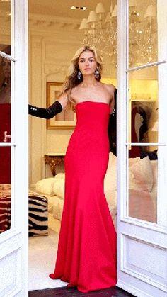 Blonde da menina animação em um vestido de noite vermelho parado na porta