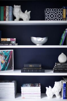 Love the navy paint and white shelves with eclectic items