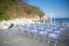 Hermoso montaje de ceremonia en playa con sillas avant garde, pasillo con quinqués o faroles y gazebo con flores. Bodas Huatulco. Playa Arrocito.