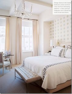 Serene yet graphic bedroom by Sara Gilbane. Love the soft blushy pinks and creams combined with the strong greek key motif on the bedding. Tall glamourous drapes, glass chandelier, tufted leather bench, and accent wall behind the bed help this space to be both modern and feminine.