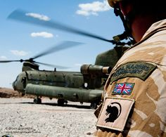 A Royal Marine Commando from 40 Cdo, waits beside a Chinook helicopter on operations in Kajaki, Afghanistan.