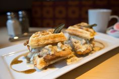Chicken and Waffle breakfast sandwich with sausage gravy and maple syrup.