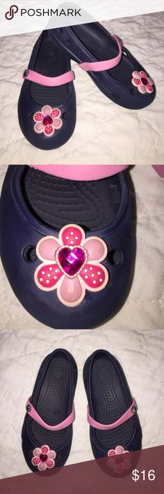 🎉HP🎉Cute Croc Mary Janes Blue Pink Gem Flower Super Cute Croc Mary Janes size 10 Navy Blue Shoe with Pink strap and cute Gem Flower Jibbitz on toes. The Flower Gem can spin so the heart Gem in middle of Flower can be faced where you would like. Pre-loved Condition. Tons of wear left. CROCS Shoes Sandals & Flip Flops