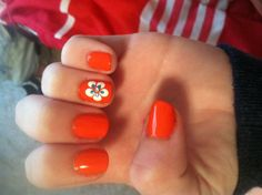 Bright orange nails with the white and blue flower and a diamond in the middle