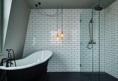 nel locale bagno, il contrasto della pietra color grigio scuro si alterna ai rivestimenti ceramici bianche presenti su alcune pareti. In primo piano due semplici lampadine a sospensione sono il sistema di illuminazione