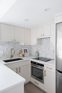 White kitchen Gold hardware Marble chevron backsplash Gold faucet Small kitchen Condo kitchen Source by architypologie The post Fairview Slopes Kitchen appeared first on Whitney DIY Design. Small Condo Kitchen, Small White Kitchens, Kitchen Room Design, Apartment Kitchen, Modern Kitchen Design, Home Decor Kitchen, Kitchen Interior, Home Kitchens, Kitchen Ideas