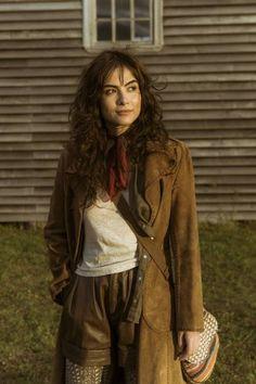 Maria Casadevall como Rimena com um look andino. Cabelo levemente cacheado, roupas largas mas ajustadas,  pouca maquiagem.
