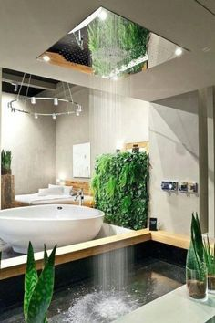 tub surrounded by plants and a waterfall