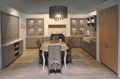 Grote landelijke keuken met lak kasten.  Bij dit ontwerp werd de keuken vooral vervaardigd uit lak in de kleur truffel. Als accent zijn de grote kolomkasten aan de zijkanten vervaardigd uit eik fineer. De keuken is opgemaakt in een U-vorm waardoor er veel ruimte ontstaat. Door het fornuis (van Boretti) in het midden te plaatsen, geeft deze keuken een warmtegevoel.