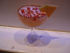 Cantoulope margarita... Garnished with a cantoulope slice.. rimmed with a sweet/spicy chili powder and topped with chamoy.....  For more cocktail pictures, follow the link and like the page.  Thanks https://www.facebook.com/pages/Damien-The-Intoxicologist-Filth/187108378032348?ref=hl