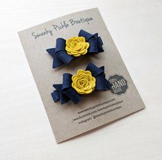 This listing is for a set of two felt flower and bow hair clips. The bows, which measure 2.5, are made of 100% wool felt and are accented by felt roses. The bows are attached to grosgrain lined alligator clips. Perfect for school uniforms or your football team. These bows are