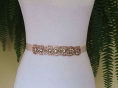 Rose Gold Demi Sash  Sparkling rose gold Demi sash is just the right size for the bride wanting to add a touch of sparkle. This crystal rhinestone sash is a beautiful rose gold and is securely fastened onto a quality double faced blush pink satin ribbon which ties into a bow and drapes down the back of your wedding dress. Perfect finishing touch for your wedding attire!  Trim measures 1.50 (3.81 cm) wide and is 7 (17.78 cm) in length. Ribbon measures 1 (2.50 cm) wide and 98 ( 2.50 meter)…