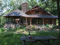 This rustic cabin features natural hardwood columns, a fantastic attached porch built of stone and gorgeous landscaping complete with a pathway and shrubbery. Enjoy a dinner for two on the picnic table on the grass and toast to a wonderful day at your wooded paradise.