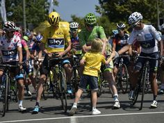 A boy shakes hands with Colombia's Nairo Quintana, wearing the best young rider's white jersey. Also in front are Australia's Richie Porte, left, wearing the best climber's polka dot jersey, Great Britain's Christopher Froome, wearing the overall leader's yellow jersey, and Germany's Andre Greipel, wearing the best sprinter's green jersey. This took place prior to the start of the 188 km 11th stage of the 102nd edition of the Tour de France race.  Lionel Bonaventure, AFP/Getty Images