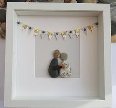 A beautiful and unique handmade pebble art picture of couple holding baby, with lovely yellow and grey bunting. This picture is a lovely home decoration and would make a perfect gift. The picture is made using pebbles, card and silver pearls. All materials are carefully placed and fixed with high strength glue onto high quality ivory hammered card. I can include printed quotes or personalised messages onto picture. If you require personalisation, before sending you the picture I will email…