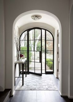 Entryway Doors with Glass and Colonial Grid Pattern also Tree Branches Decor on Tall Flower Vases Over Narrow Hallway Table Above Wide Plank Flooring also Entryway Storage Bench Narrow Entryway Storage Narrow Hall Table