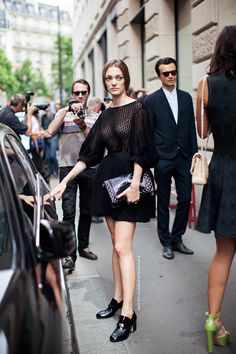 Sofia Sanchez Barrenechea in a black crochet lace dress with billowing sleeves and patent high heel loafers.
