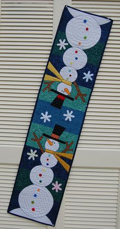 Brighten up your dining space with this whimsical snowman Table Scarf. The two tall snowmen have long gold scarves around their necks, and tall black top hats, and they are ready to dance around. Machine appliqued with a blanket stitch onto a pieced background of light and dark turquoise fabrics that are mixed with three different shades of blue, they look as if they are trying to catch the large snowflakes falling from the sky. A hand sewn dark blue, double folded binding, and buttons in…